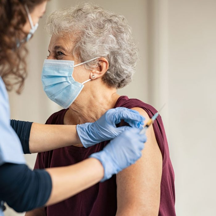 General practitioner vaccinating a senior woman with the Covid-19 or coronavirus vaccine.