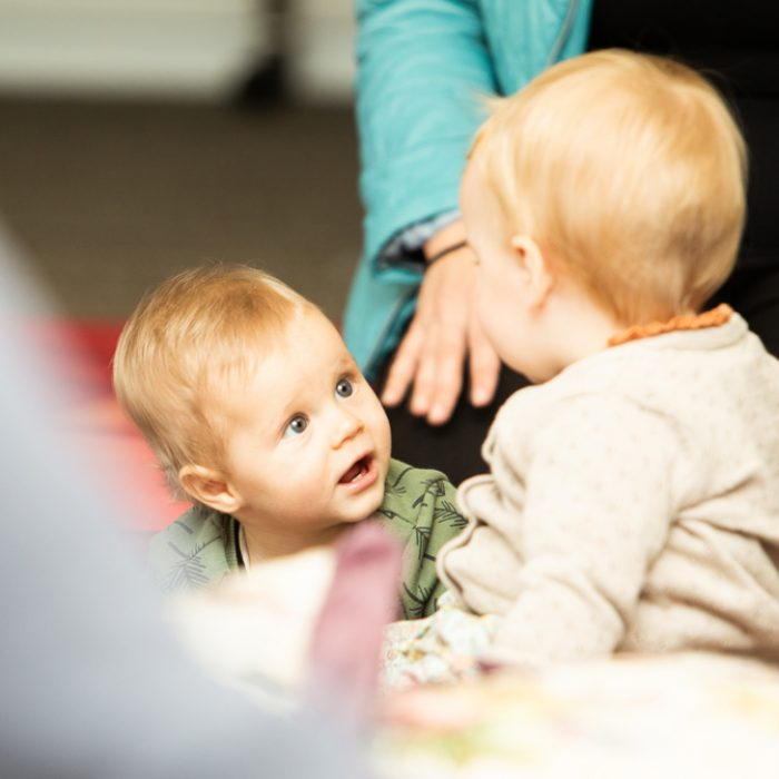 Close up of a baby at a baby class looking at another baby