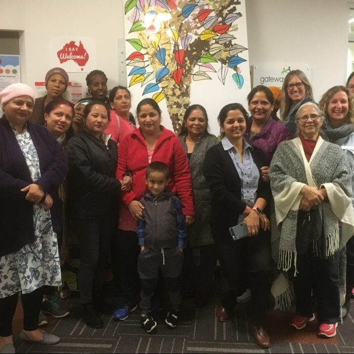 Group of women and one child from multicultural communities standing in front of image of a large tree with multi coloured leaves